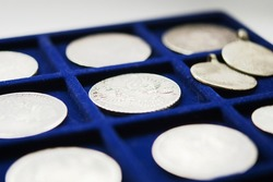 Blue color tray with silver coins for numismatic research isolated on white background
