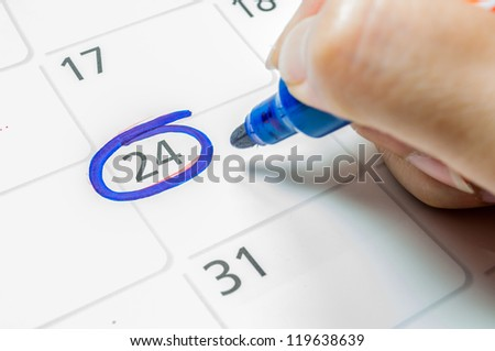 Blue color writing on the calendar at 24. - stock photo