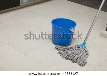 Blue colored mop cleaning tiled floor