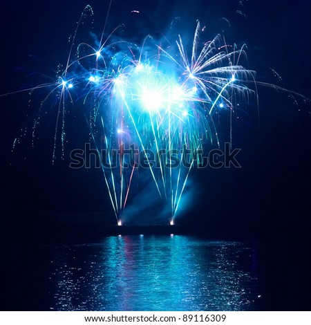 Blue colorful fireworks on the black sky background. Holiday celebration.