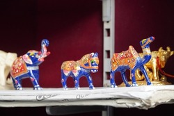 Blue coloured Elephant, camel, horse figurines displayed for sale in a shop. Various Traditional local handicraft. Selective focus.