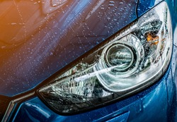 Blue compact SUV car with sport and modern design are washing with water. Car care service business concept. Car covered with drops of water after cleaning with high pressure water spray