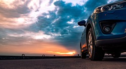 Blue compact SUV car with sport and modern design parked on concrete road by the sea at sunset. Environmentally friendly technology. Car parking space. Hybrid and electric car technology concept.