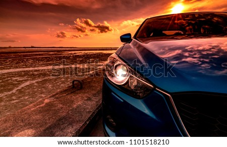 Blue compact SUV car with sport and modern design parked on concrete road by the sea at sunset. Environmentally friendly technology. Business success concept. Car with open headlamp light.