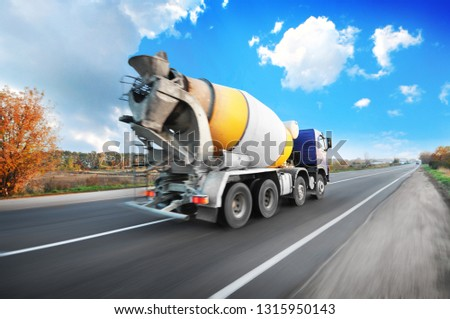 Blue concrete mixer truck driving fast on the countryside road with trees against blue sky with clouds #1315950143
