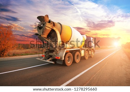 Blue concrete mixer truck on the countryside road with trees against night sky with sunset #1278295660