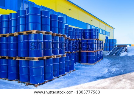 Blue containers are palletized in stock. Metal barrels for chemicals. Barrels are ready to be shipped from stock. Warehouse shipping activities. Chemical industry.