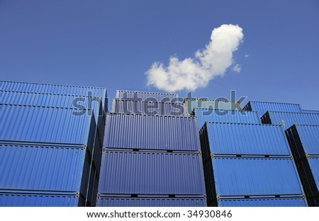 Blue containers waiting to be loaded against a clear blue sky with one white cloud. No names on the containers