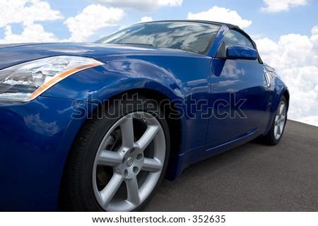 Blue convertible sporstcar with a blue cloudy sky background. #352635