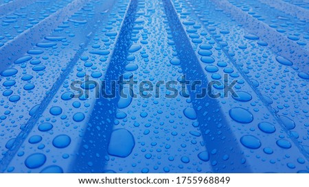 Blue corrugated sheet with drops of water. Close-up