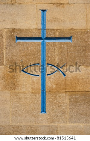 Blue cross and fish carved into stone, a symbol of christianity