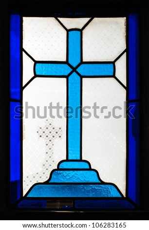 Blue cross on the glass window in a cemetery