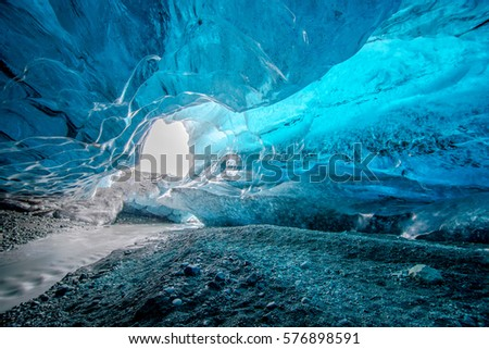 Blue crystal ice cave and an underground river beneath the glacier in Iceland