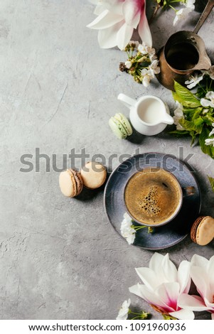 Blue cup of black espresso coffee french dessert macaroons, cream and spring flowers magnolia, blooming cherry branches over grey texture background. Top view, space. Spring greeting card