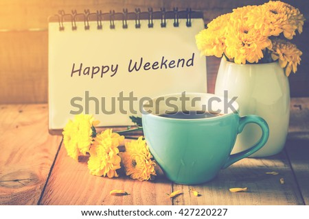 Photo of  blue cup of coffee on wooden floor with yellow flower in white pot and happy weekend note on morning sunlight. vintage color tone, happy weekend concept.