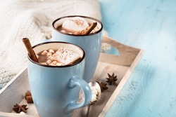 Blue Cup of hot Chocolate drink with Marshmallows and cinnamon on blue wooden background. Winter time. Holiday concept, Selective focus