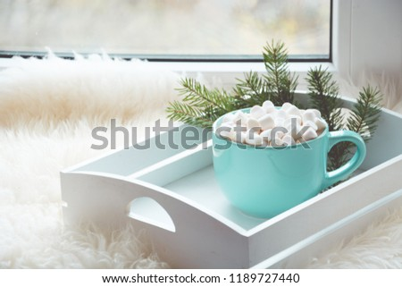 Blue cup of hot chocolate with marshmallow on windowsill with furskin for relax. Holiday concept. Home style. - Shutterstock ID 1189727440
