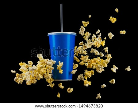 Blue cup with cap and flying popcorn isolated on black background. Concept of refreshments in cinema or watching movies #1494673820