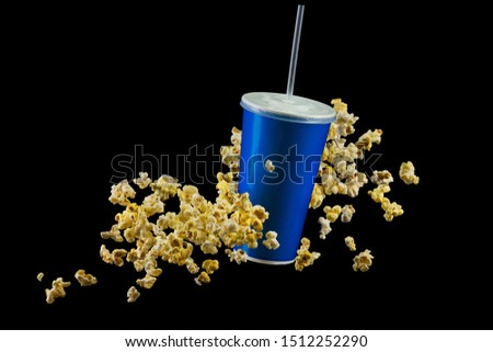 Blue cup with cap and flying popcorn isolated on black background. Concept of refreshments in cinema or watching movies #1512252290