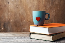 blue cup with red heart on green and orange books on grunge wooden table