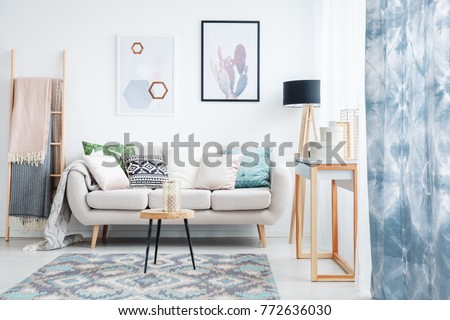 Blue curtain, posters and carpet in living room with blankets on ladder next to sofa with pillows #772636030