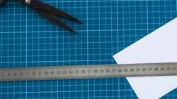 blue cutter mat with scissors, paper and ruler