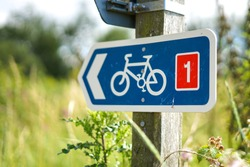 Blue Cycle Path sign on wooden post. Green field in the backgrond. Holkham Beach, Norfolk, UK -Image