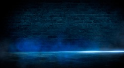 Blue dark background of empty foggy street with wet asphalt, illuminated by a searchlight, laser beams, smoke