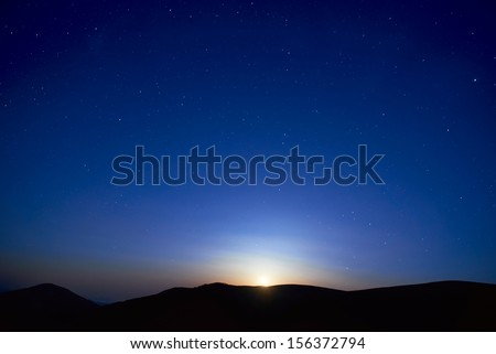 Blue dark night sky with many stars. Moon rising. Space background