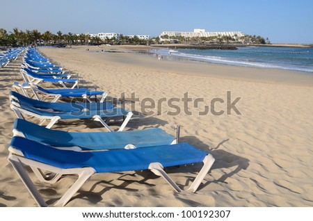 Blue deck chairs on tropical beach
