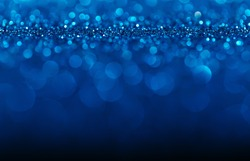 Blue defocused glitter background with bokeh copy space