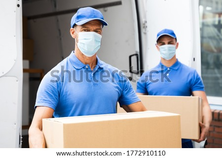 Blue Delivery Men Unloading Package From Truck With Face Mask Photo stock ©