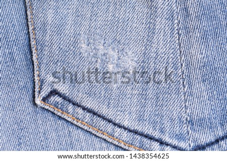 Blue denim. Cotton fabric, jeans. Creative vintage background. Pocket and zipper. The line is of poor quality. Cheap item