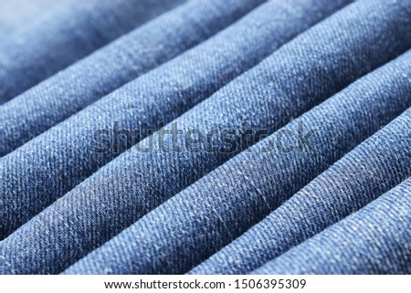Blue denim folded fabric background. Jeans material placed in diagolnal folds. Closeup. Selective focus #1506395309