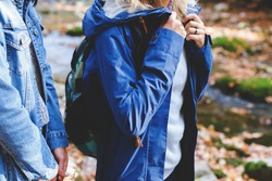 Blue denim jacket and parka. Clothing for the camping trip. Hiking clothes. Two young girls friends walking in the autumn forest. Walk in the woods at fall.