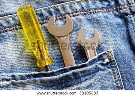 Blue denim jean pocket with spanners and screwdriver - stock photo