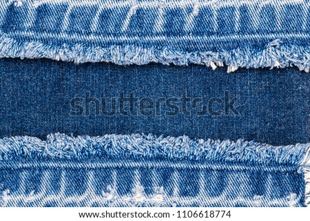 Blue denim jeans fabric frame. Bleached denim fabric with fringe edge on blue denim background, text place, copy space. Worn Jeans Casual Double Color patch