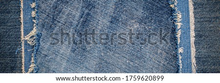Blue denim jeans fabric patch on jean cloth background. Word Casual Double Color Patchwork Denim. Destroyed denim blue fabric patch on blue jeans background. Worn Jean Casual Denim, banner