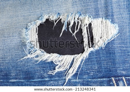 Blue denim jeans in bright color in the scene present the old denim look and old damaging fabric that shown detail of texture background.