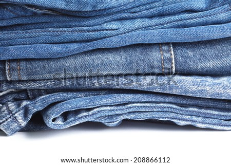 Blue denim jeans many pairs in bright color tone fold and stack up together.