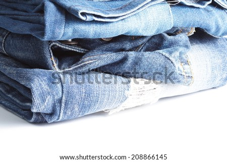 Blue denim jeans many pairs in bright color tone fold and stack up together. In the scene present the tear up surface to show the old and vintage style texture background.