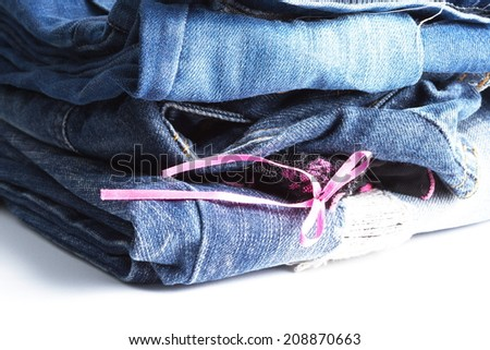 Blue denim jeans many pairs in bright color tone fold and stack up together. In the scene present the black color pantie with pink ribbon between the layer of folding jeans.