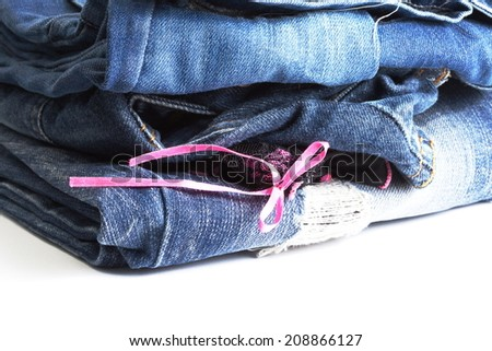Blue denim jeans many pairs in dark color tone fold and stack up together. In the scene present the black color pantie with pink ribbon between the layer of folding jeans.