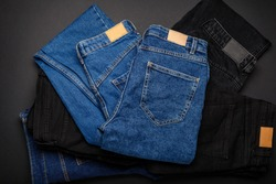 Blue denim jeans on pile of jeans pants. Top view of variety of denim jean textiles on black background. Many jean trousers pants.
