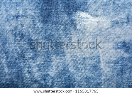 Blue denim texture with holes and threads