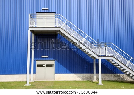 Blue Depot factory with green grass - stock photo