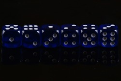 Blue dice on a black background. Game addiction. Luck