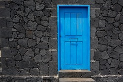 Blue door in black lava stone masonry wall at La Palma Canary Islands