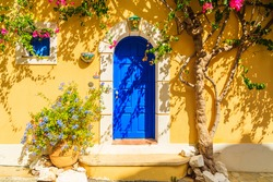 Blue door of a yellow Greek house decorated with flowers, Assos town, Kefalonia island, Greece