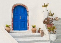 blue door of beautiful white Greek house with flower pots on stairs in city of Oia, Santorini (Thira), Greece